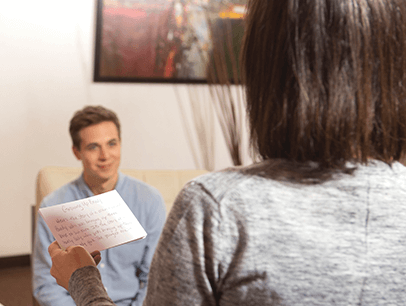 Woman with notecard speaking to man