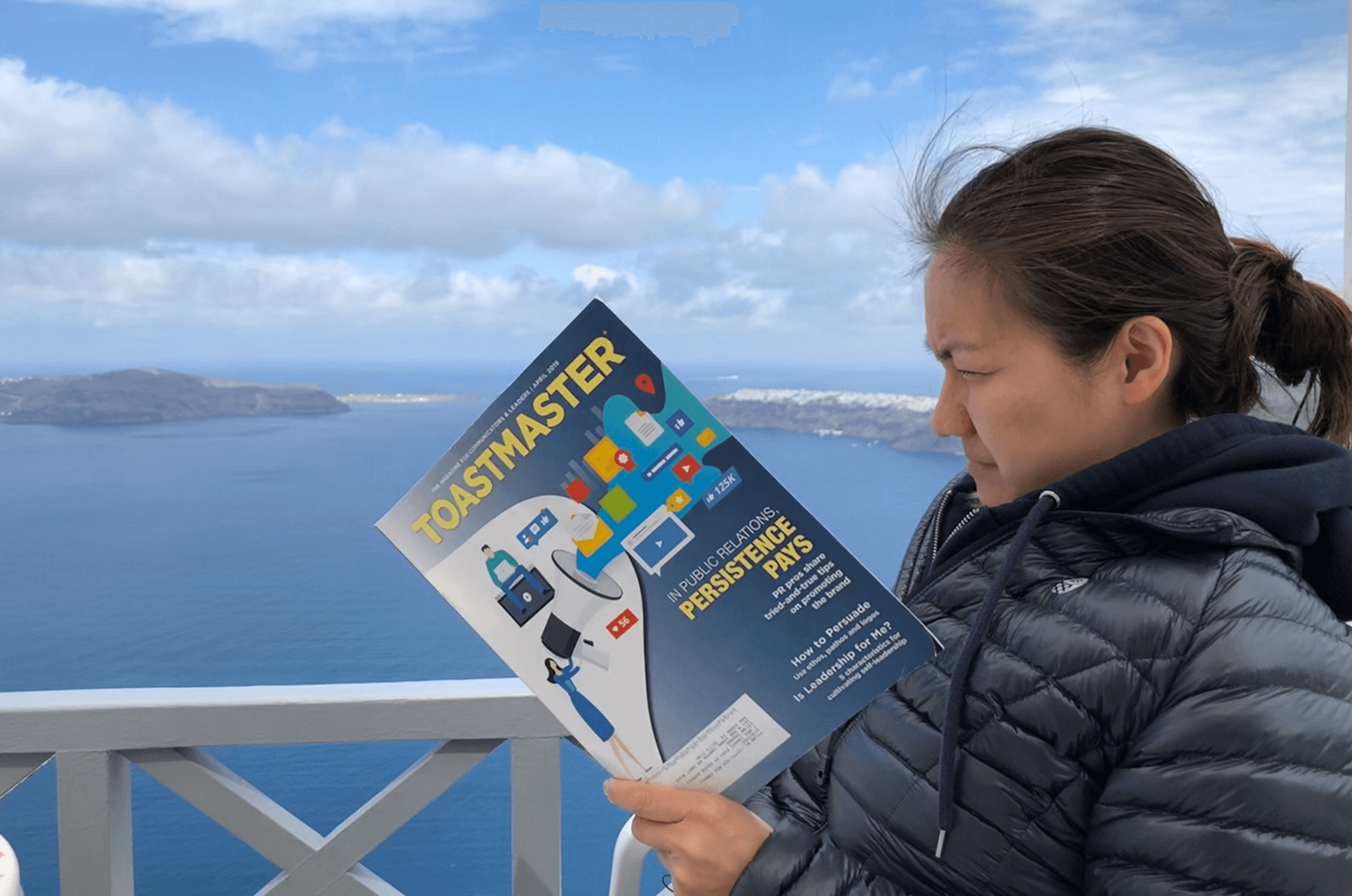 Lefan Zhuang of San Dimas, California, reads her Toastmaster magazine on the balcony of her hotel in Imerovigli, Greece. The white buildings in the background are part of the city of Oia.
