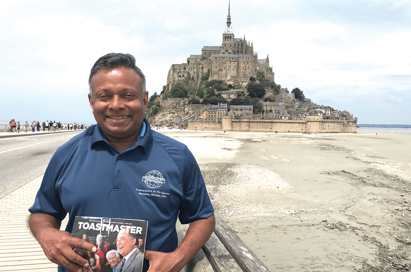 Manuja Ranasinghe, DTM, of Roswell, Georgia, poses in front of the Abbey at Mont-Saint-Michel—an island connected to Normandy, France.