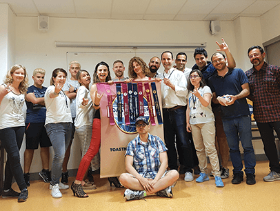 Group of Toastmasters members in Spain pose with banner