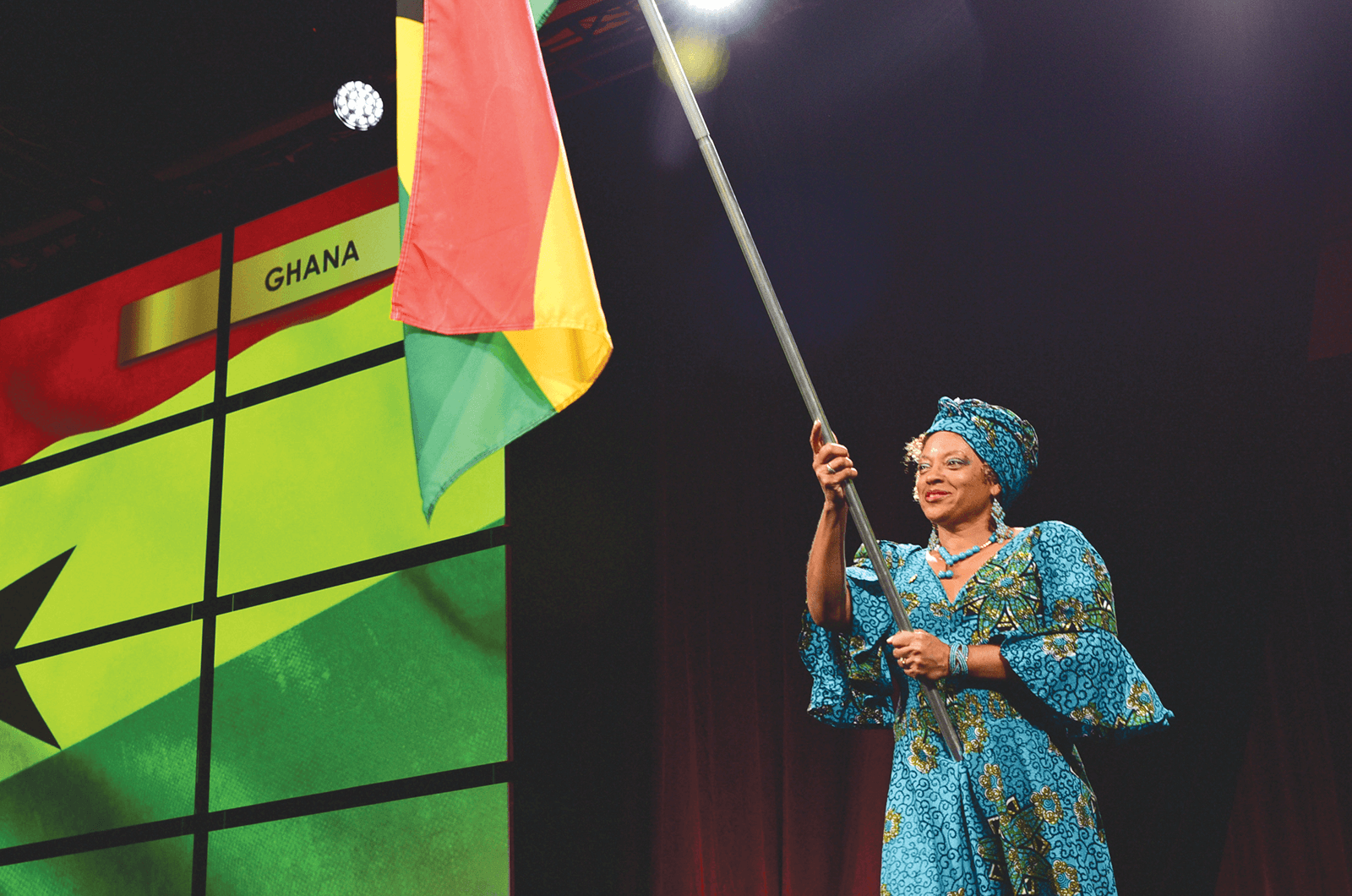A Toastmaster from Ghana holds the country flag during Opening Ceremonies.
