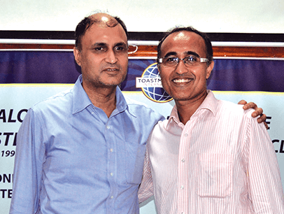 Man in blue shirt posing with mentor
