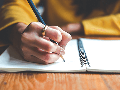 Person writing with a pencil in a notebook