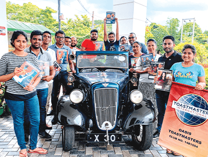 Toastmasters members holding magazine while posing next to 1927 car