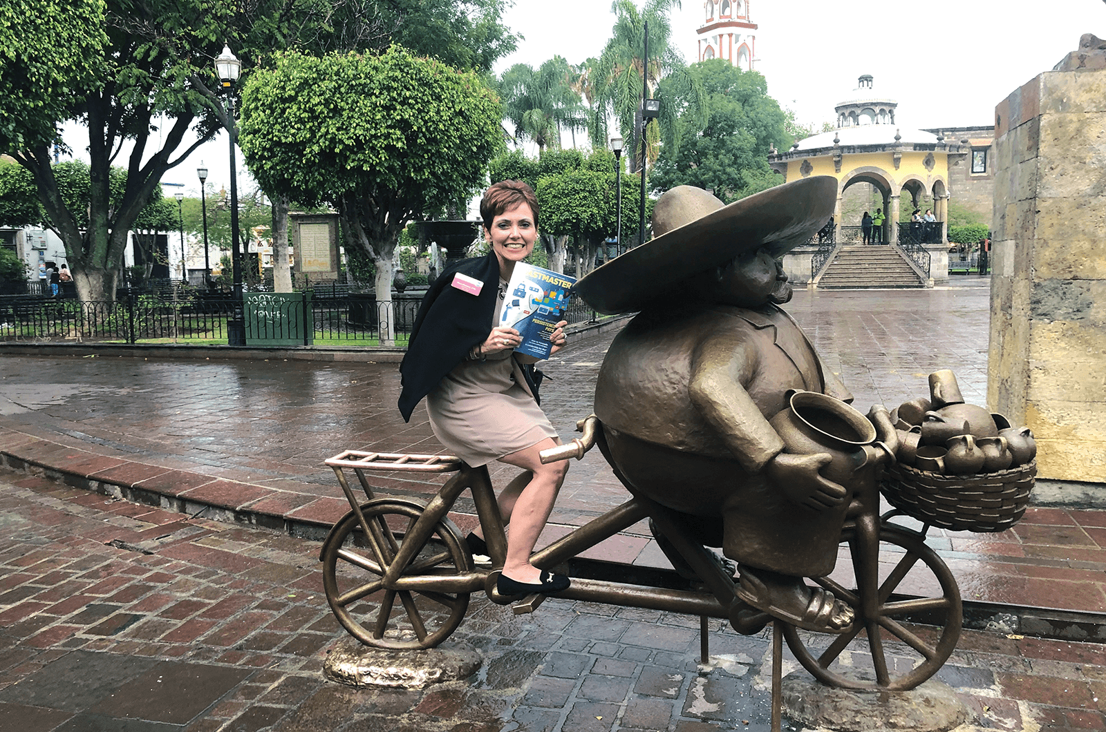 Maria Martinez, DTM, of Lakeland, Florida, poses on a statue of a peddler on a bicycle in Guadalajara, Mexico.