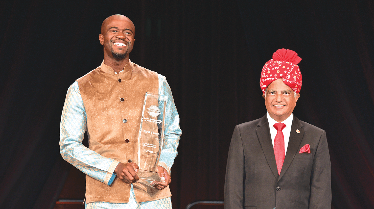 Beverly reacts happily after being announced by International President Deepak Menon (right) as the 2019 World Champion of Public Speaking.