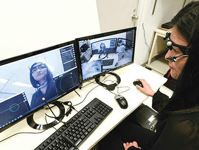 Woman at computer monitoring eye movements