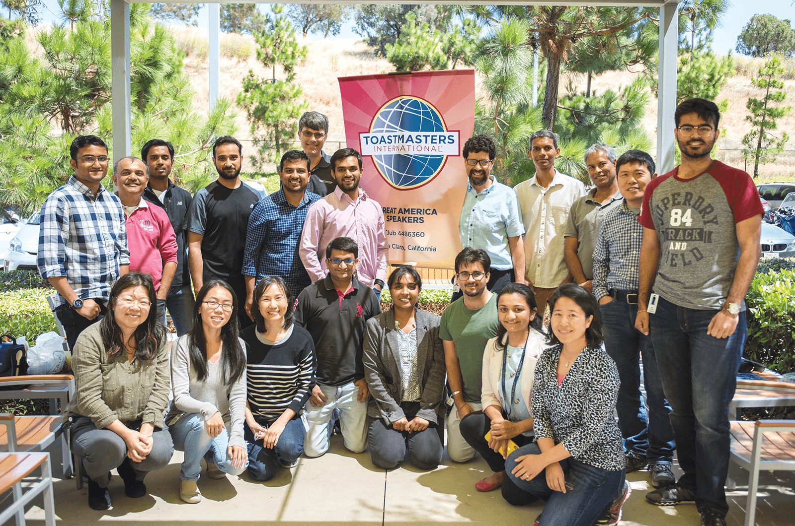 Group of Toastmasters members posing outdoors with banner