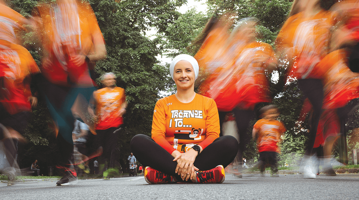 Woman in orange shirt sitting on pavement