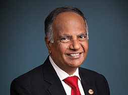 Toastmasters International President Deepak Menon in suit and red tie
