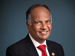 Toastmasters International President Deepak Menon in suit and red tie