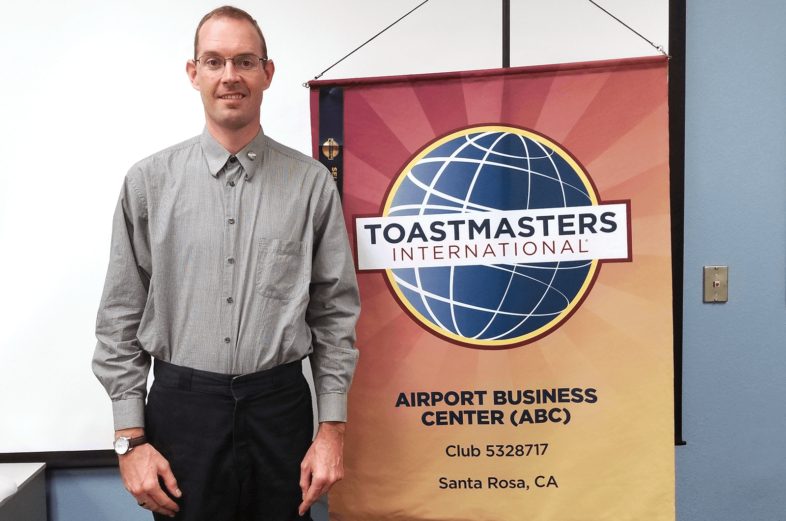 Toastmaster member standing next to club banner