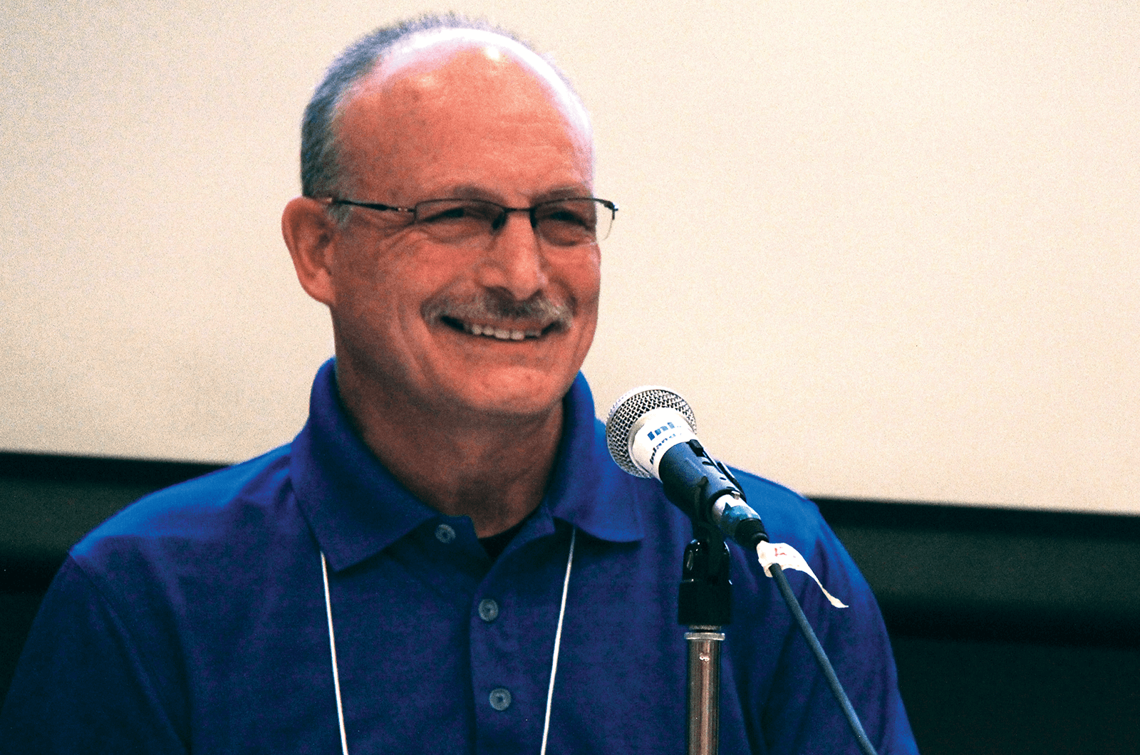 Man in blue shirt smiling in front of microphone