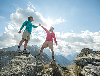 Man and woman high-five on top of mountain