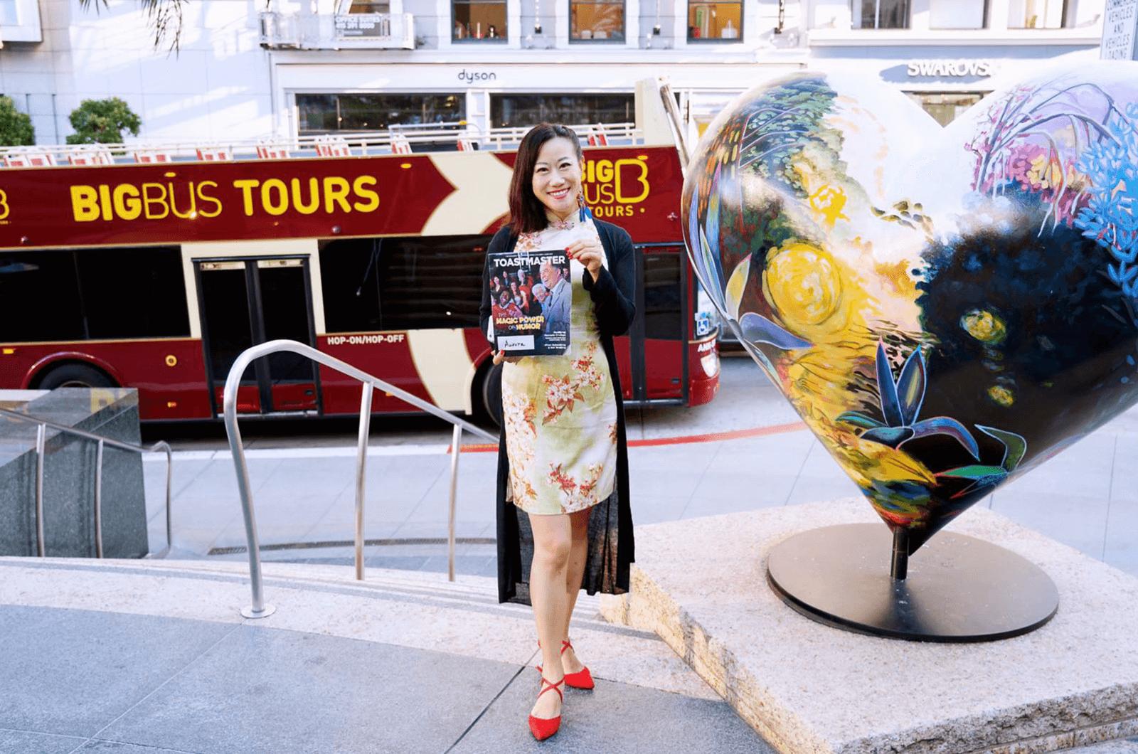 Aurora Zheng of Qingdao, Shandong, China, takes a photo alongside a heart sculpture in San Francisco's Union Square in California.