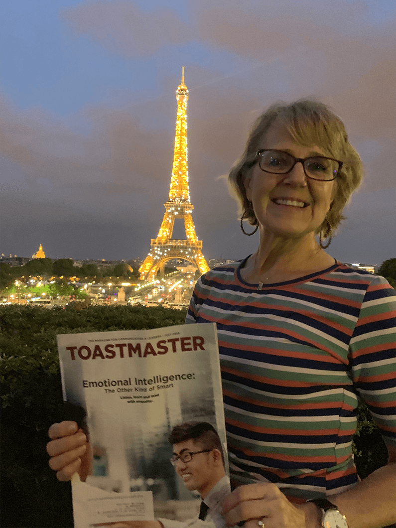 Becky Tripp of Amherst, New Hampshire, poses with her Toastmaster in front of the Eiffel Tower in Paris, France.