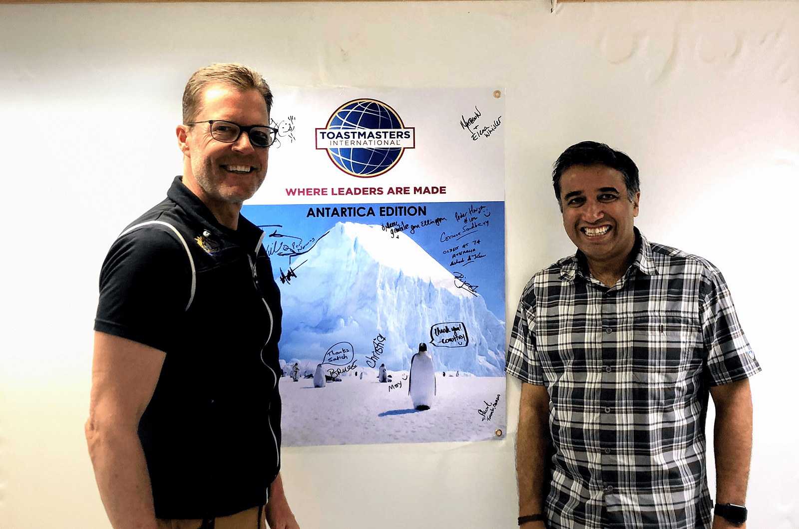Satish (right) poses with a fellow marathon runner on the ship to Antarctica after holding a demo Toastmasters meeting.
