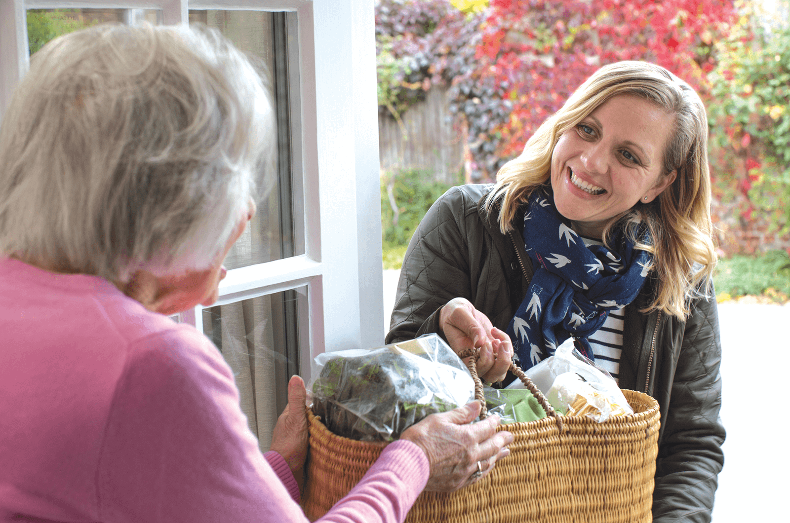 Younger woman hands older woman a basket of food