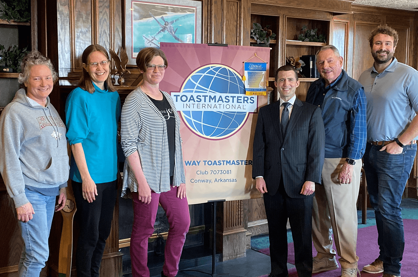 Toastmasters members pose with club banner