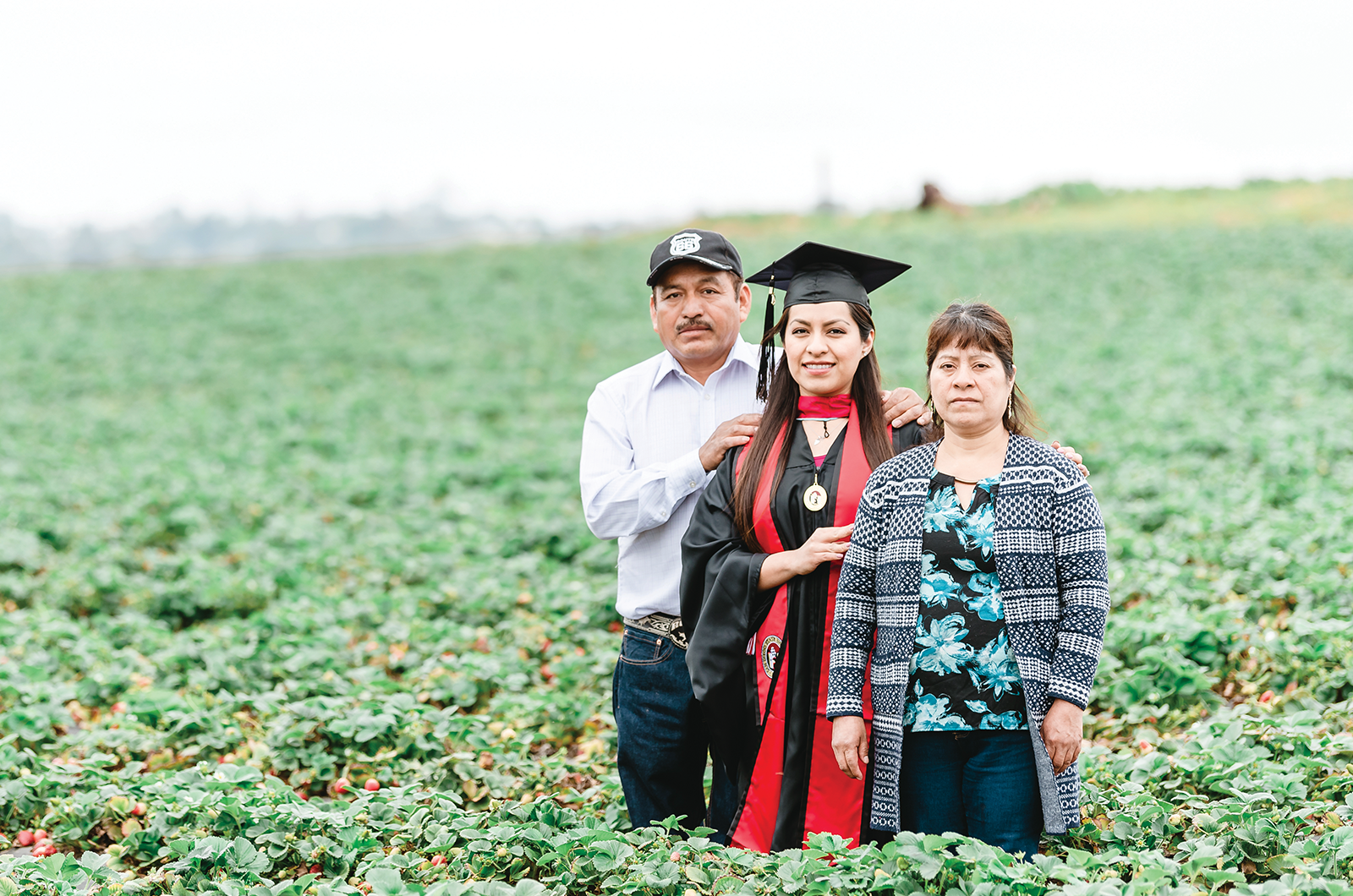 College grad stands in fruit field with parents