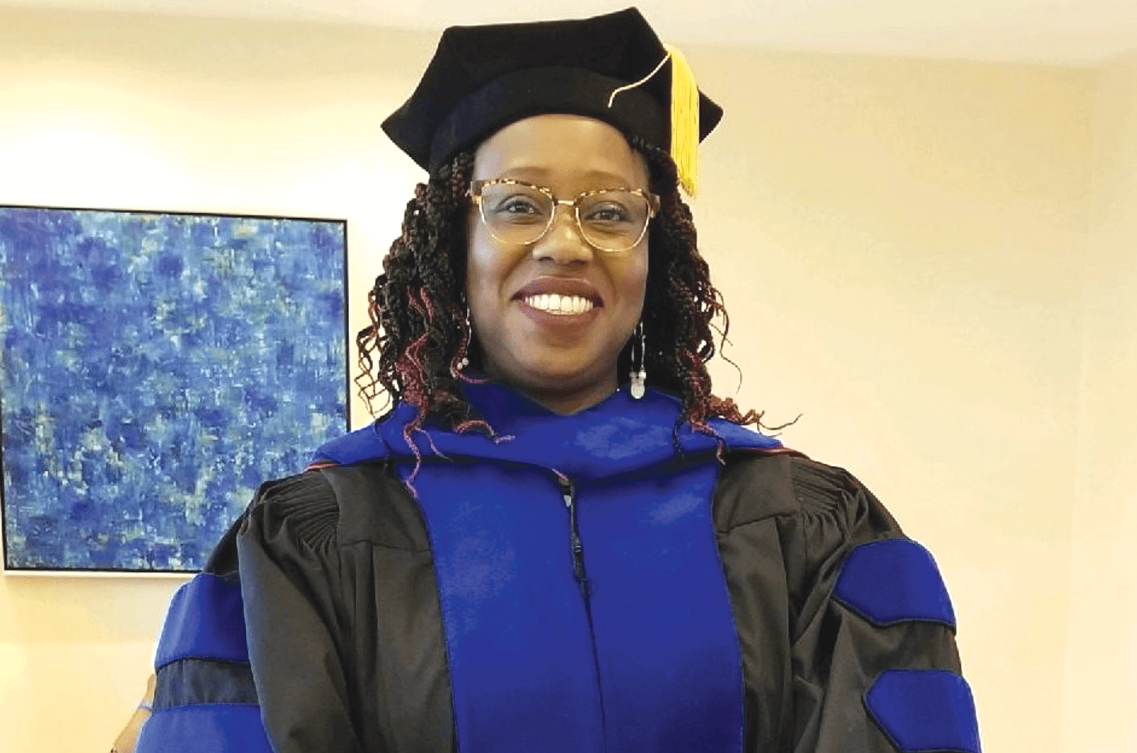 Woman in blue graduation cap and gown