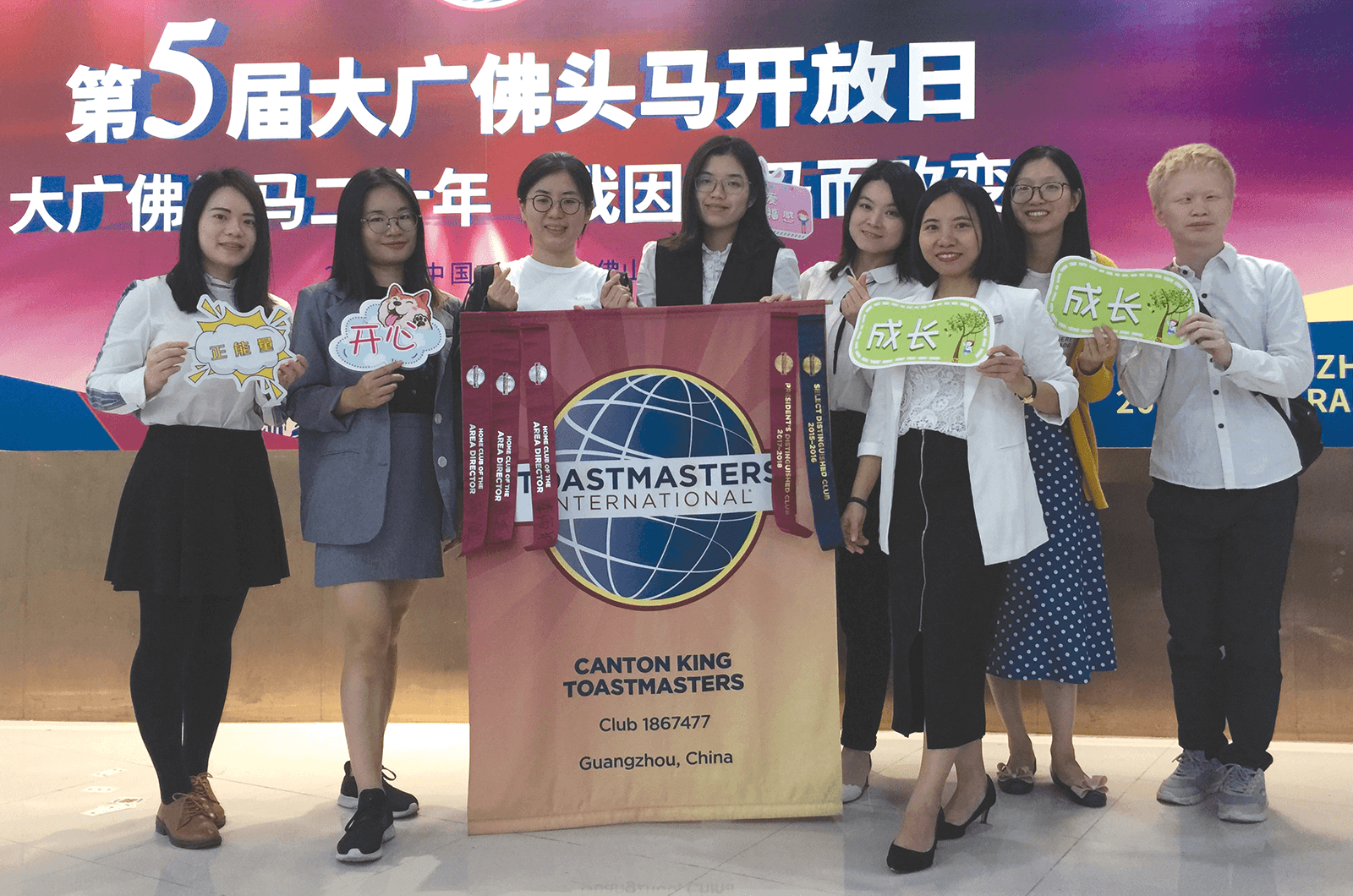 Group of Toastmasters holding club banner and signs