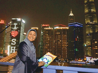 Julia Taha of Selangor, Malaysia, strolls along the Bund waterfront in Shanghai, China, and takes in the night scene, including the landmark Pearl TV Tower, lit in blue.