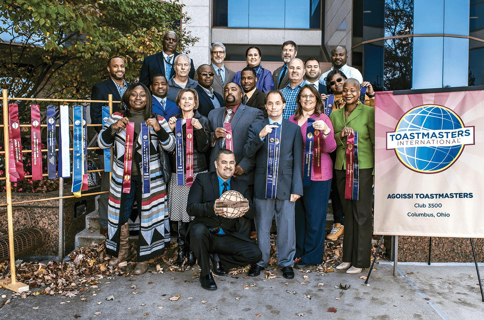 Group of Toastmasters members standing outside next to banner and ribbons