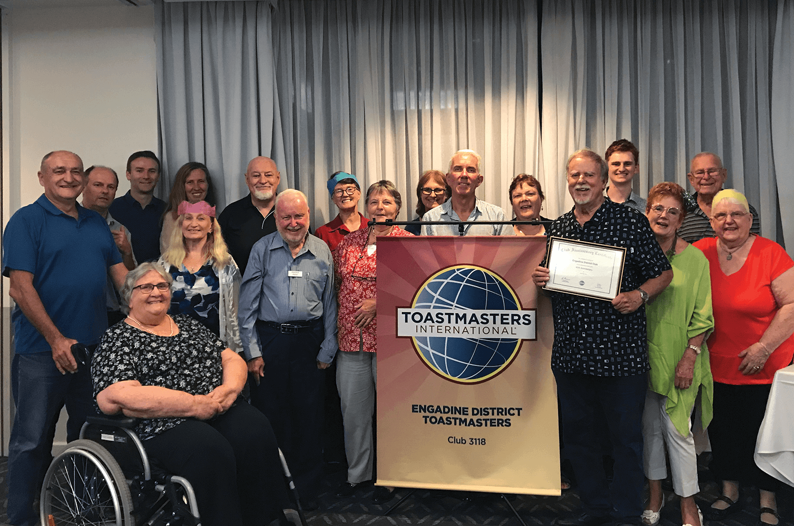 Group of Toastmasters members posing with banner