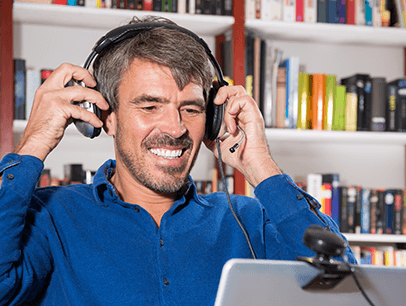 Man in blue shirt adjusting headphones while videoconferencing