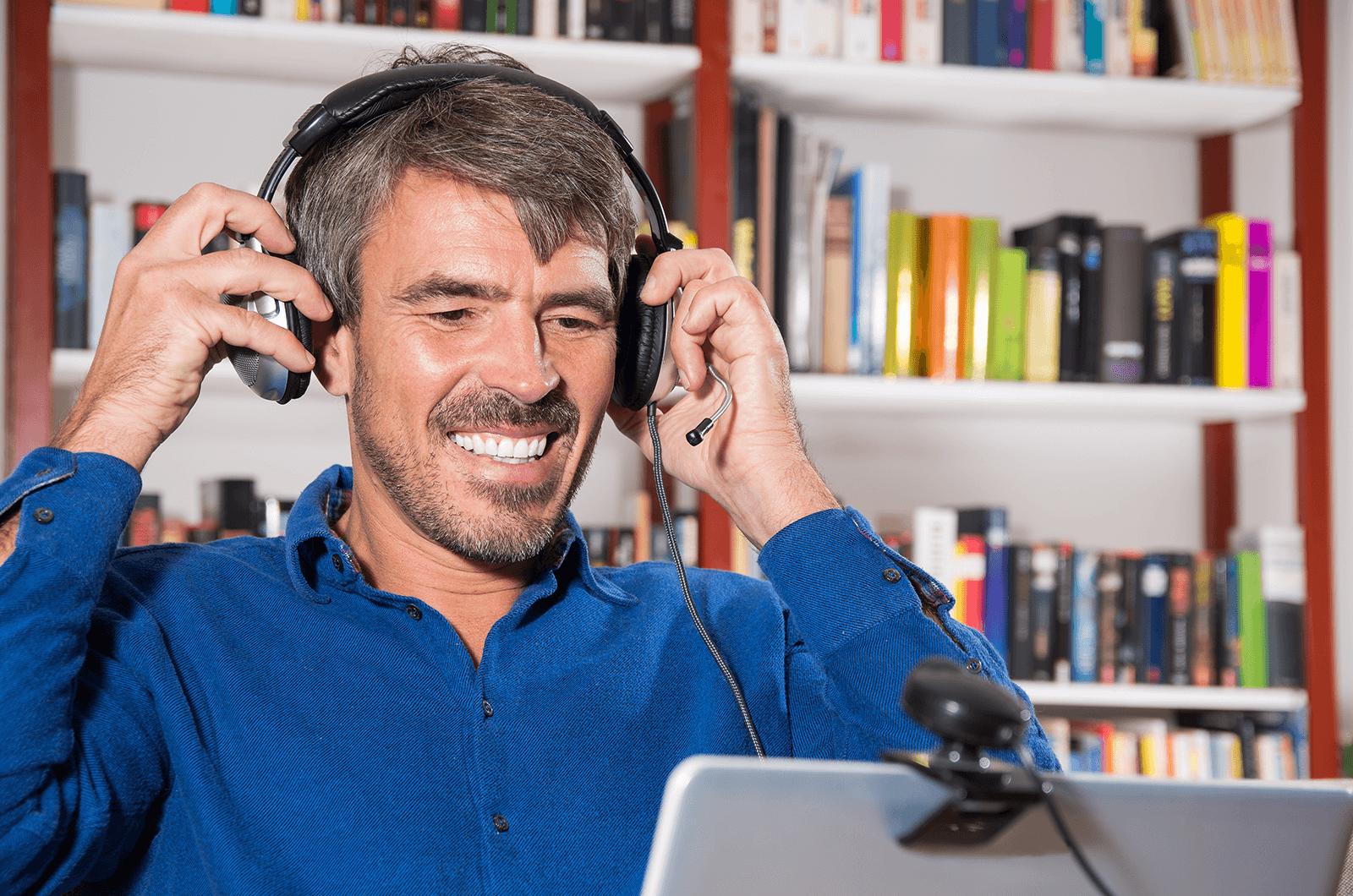 Man in blue shirt adjusting headphones while videoconferencing