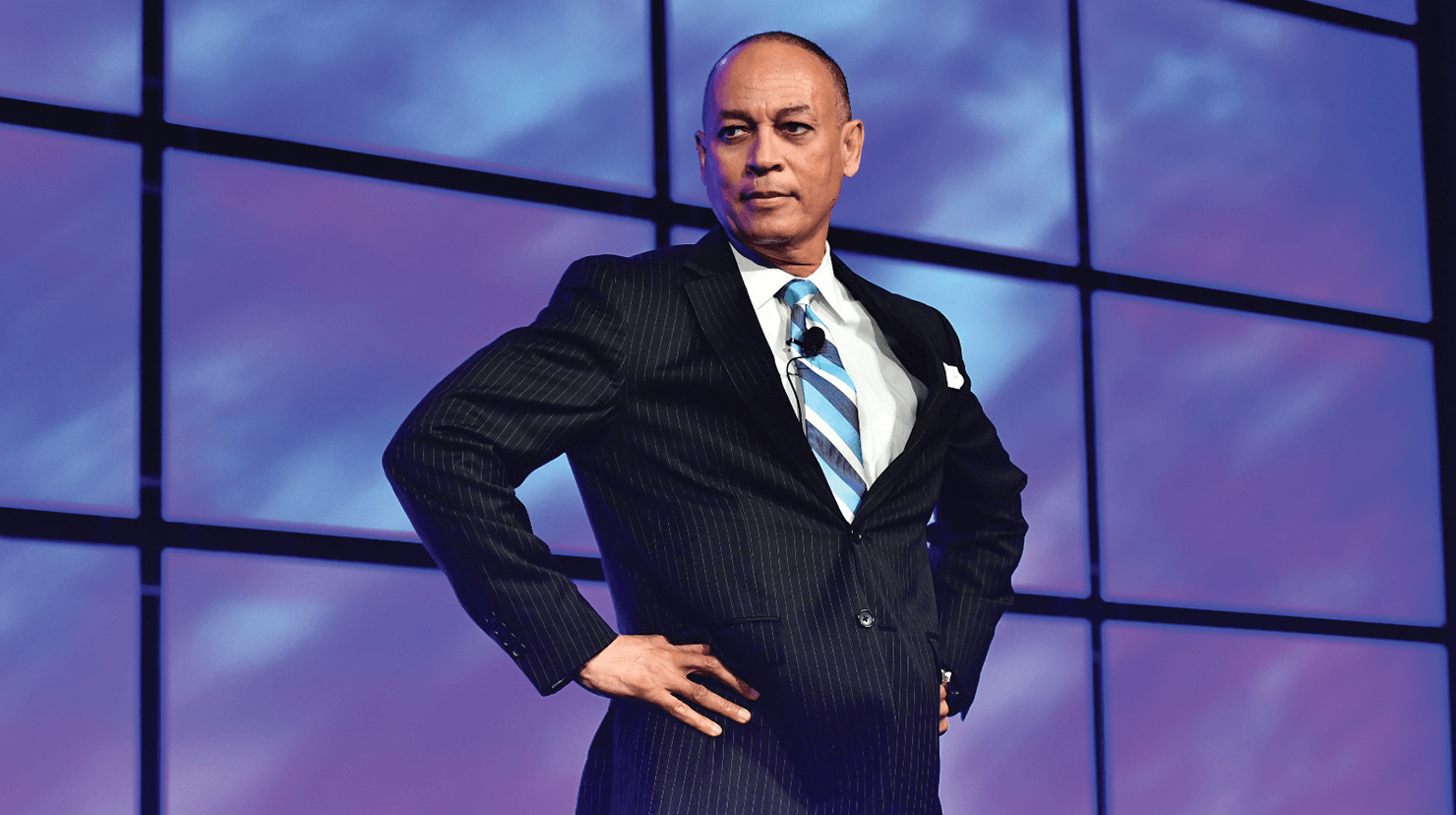 Ed Tate dressed in a suit and tie strikes a power pose onstage
