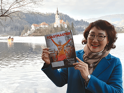 Seunghee Lisa Han, DTM, of Daegu, Korea, poses with her magazine at Lake Bled in northwestern Slovenia.
