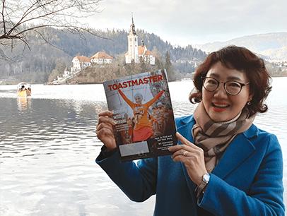 Seunghee Lisa Han, DTM, of Daegu, Korea, poses with her magazine at Lake Bled in northwestern Slovenia.