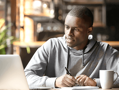 Young man in sweatshirt looking at laptop and taking notes on paper at home