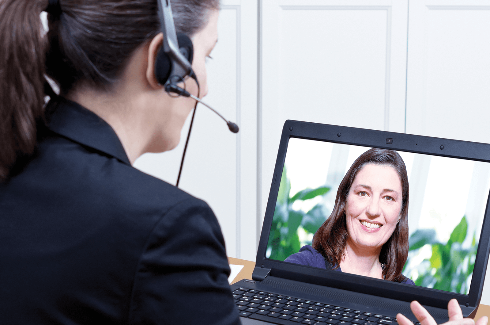 Woman wearing headset interviewing with another woman on laptop