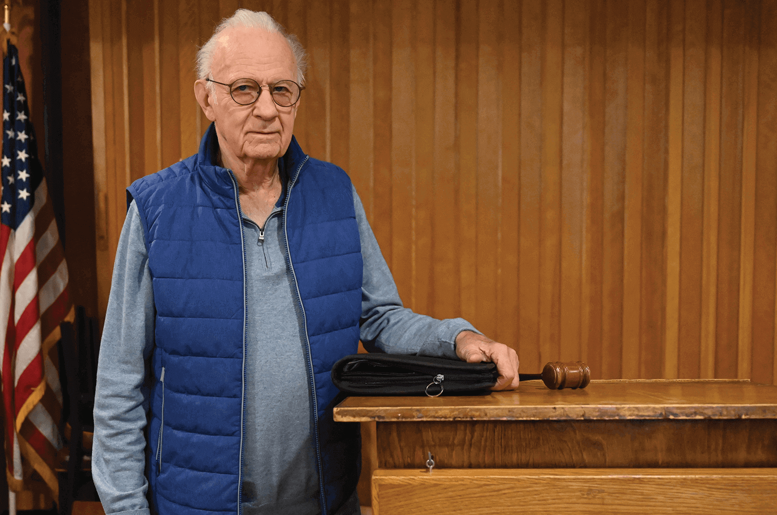 Man in blue vest standing at lectern with gavel