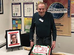 Man posing with banner and cake