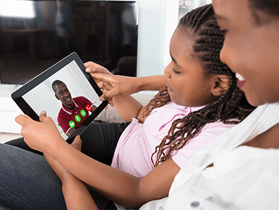 Mother and daughter sitting together and talking to male on iPad