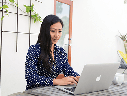 Woman in polka-dot shirt working on computer