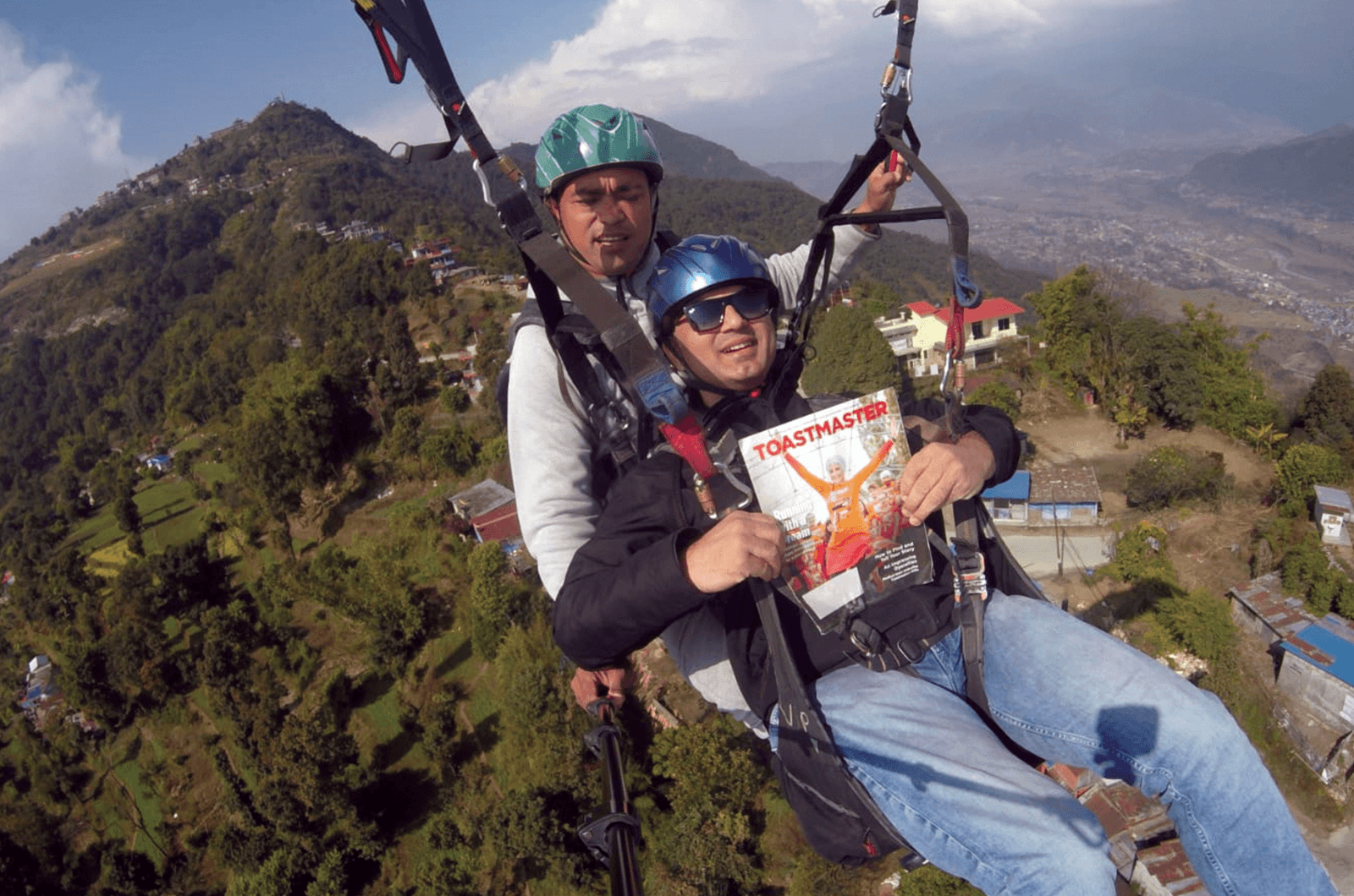 Ajay Kumar Mohapatra of Pune, Maharashtra, India, paraglides with his magazine and an instructor in Pokhara, Nepal.