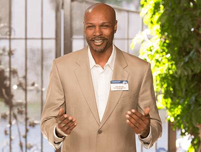 Man in tan suit jacket speaking with gestures