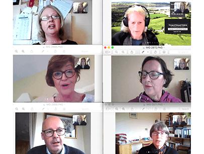 Six Toastmasters members speaking on their computers during online meeting