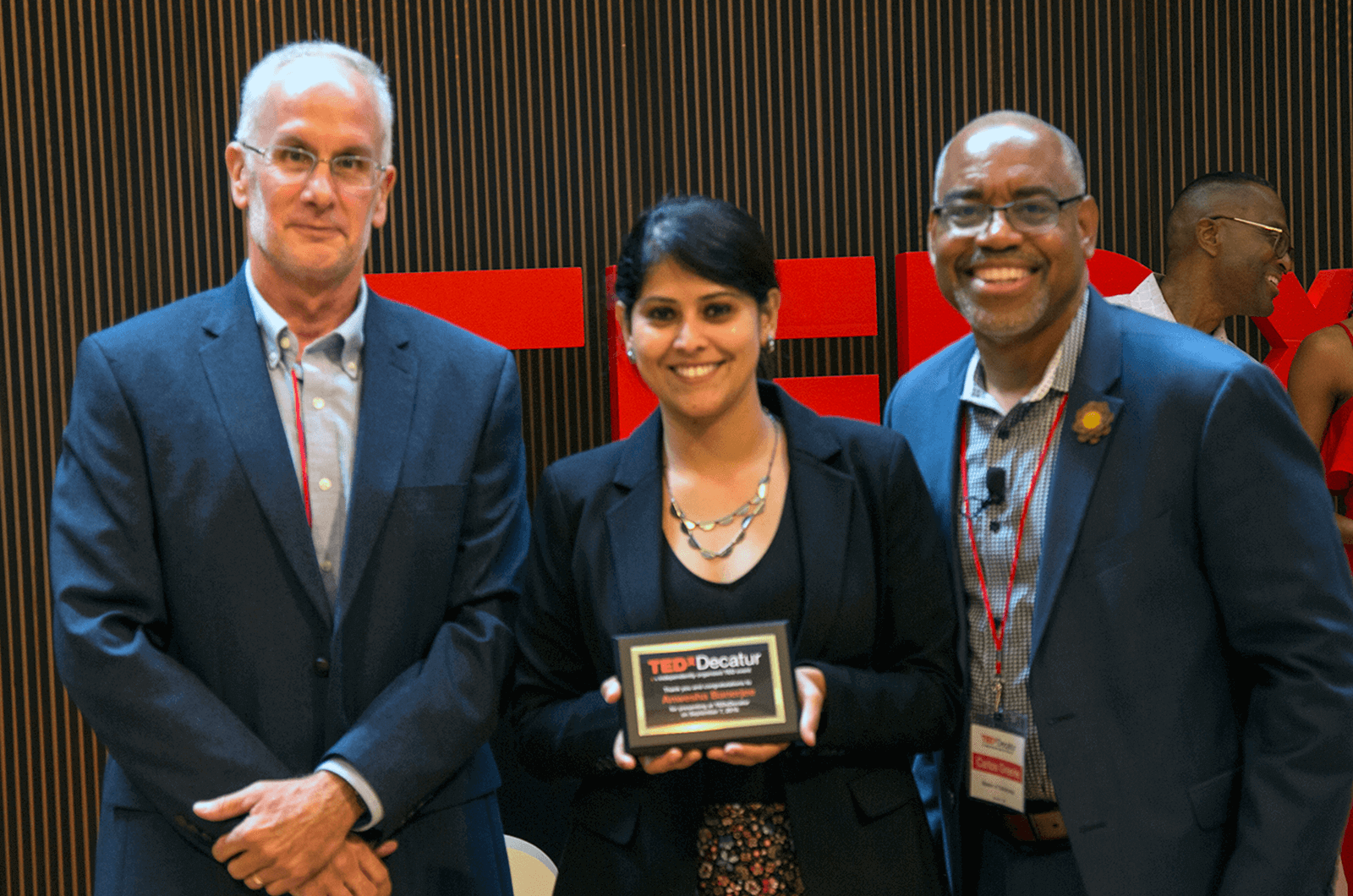 Anwesha Banerjee stands in between Toastmasters Carlos Greene and Daniel Enger while holding a plaque