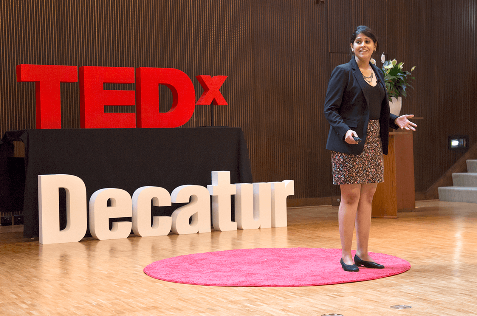 Anwesha Banerjee stands on red dot on TEDx stage