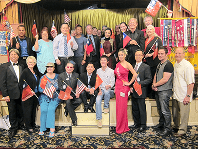 A group of members from the Renaissance Speakers Toastmasters club pose with banners and flags