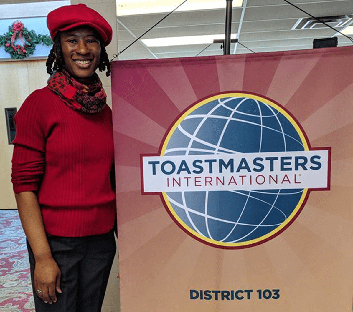 Cassandra lee in red shirt and hat standing next to Toastmasters banner