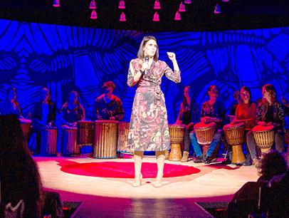 Elena Paweta giving speech on red dot on TEDx stage