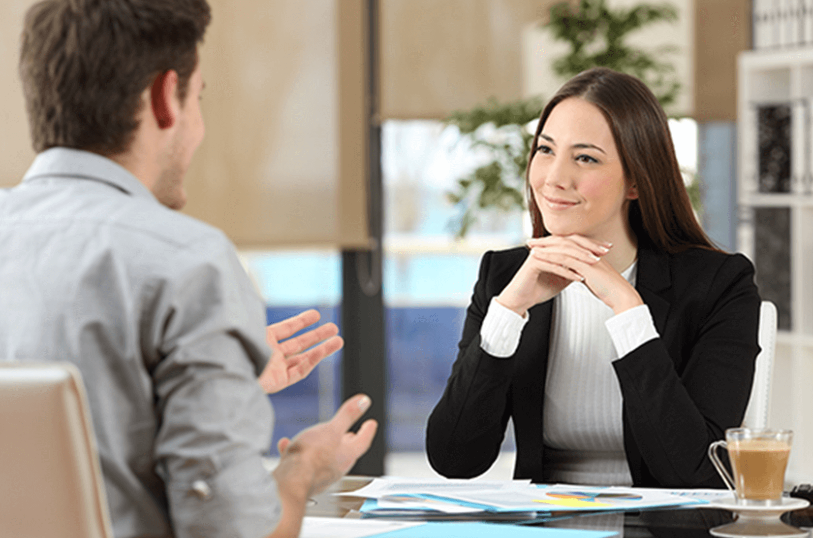 Woman with hands clasped listening to man speak