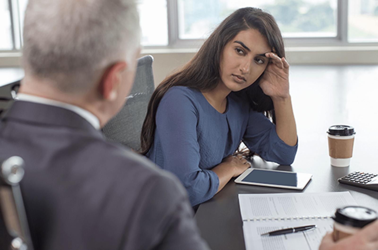 Woman in blue shirt receiving feedback from man